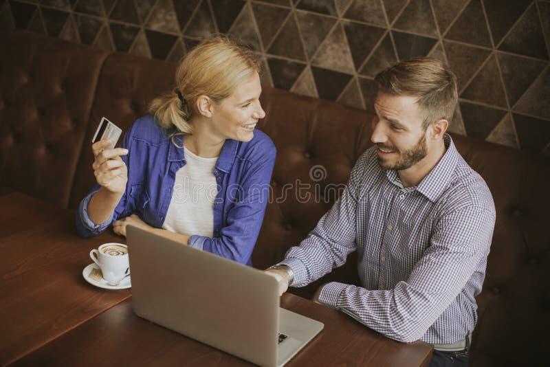 Jeunes ajouter à l'ordinateur portable dans le restaurant photo libre de droits