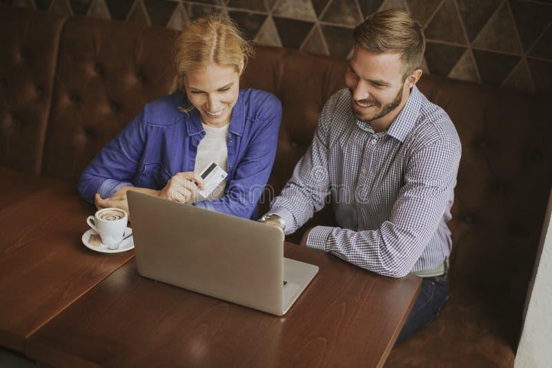 Jeunes ajouter à l'ordinateur portable dans le restaurant photo stock