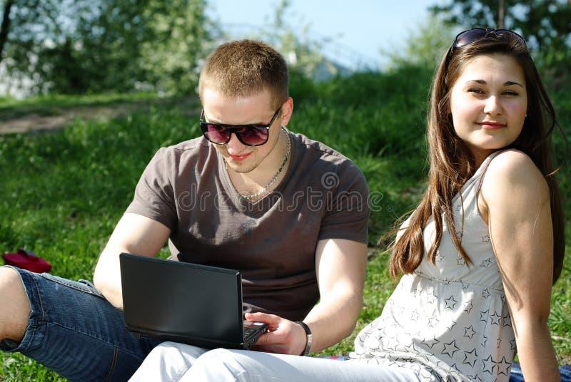 Jeunes ajouter à l'ordinateur portatif photo stock