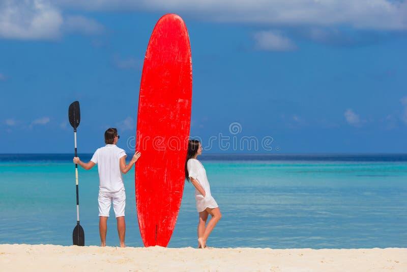Jeunes ajouter à la planche de surf rouge pendant le tropical photos stock