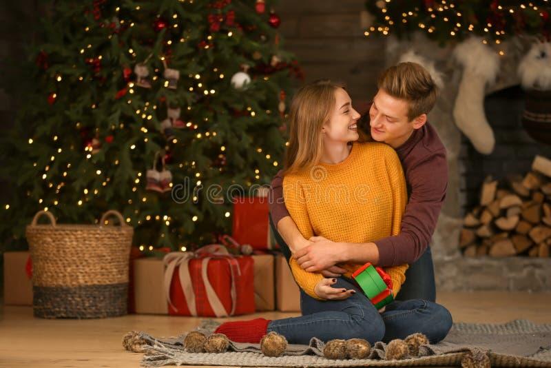 Jeunes ajouter aimants au cadeau dans la chambre avec le décor de Noël photos libres de droits