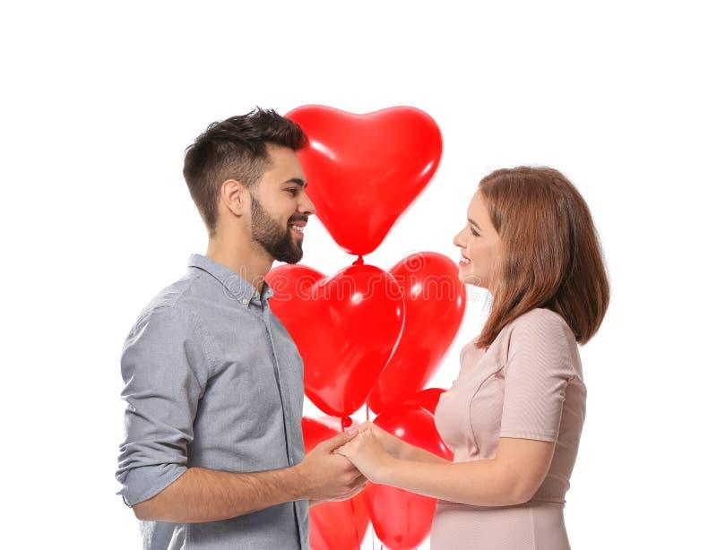Jeunes ajouter aimants aux ballons en forme de coeur sur le fond blanc Célébration de Saint-Valentin de saint image stock