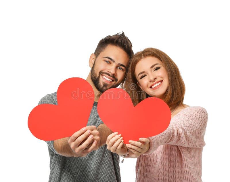 Jeunes ajouter aimants aux coeurs rouges de papier sur le fond blanc Célébration de Saint-Valentin de saint photographie stock libre de droits