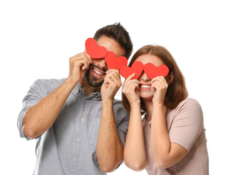 Jeunes ajouter aimants aux coeurs rouges de papier sur le fond blanc Célébration de Saint-Valentin de saint photos libres de droits