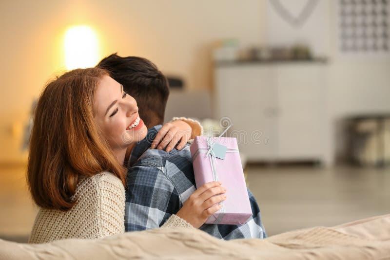 Jeunes ajouter au boîte-cadeau étreignant à la maison Célébration de Saint-Valentin de saint images stock