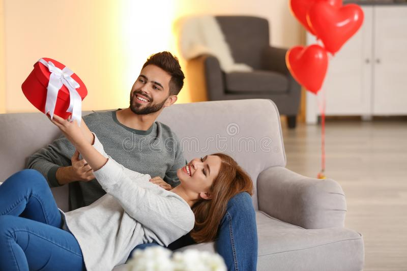 Jeunes ajouter au boîte-cadeau sur le sofa à la maison Célébration de Saint-Valentin de saint photographie stock libre de droits