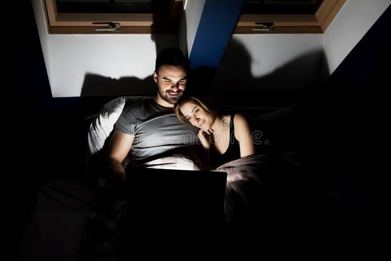 Jeunes ajouter au film de observation d'ordinateur portable dans le lit photos libres de droits