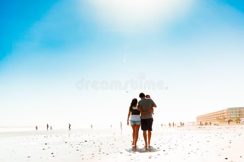 Jeunes ajouter au fils de bébé marchant sur la plage blanche le jour ensoleillé d'été images stock