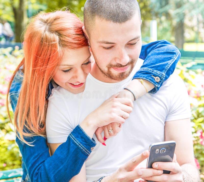 Jeunes ajouter au téléphone portable au parc image stock