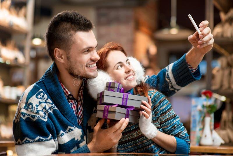 Jeunes ajouter aux boîte-cadeau au café en hiver image stock