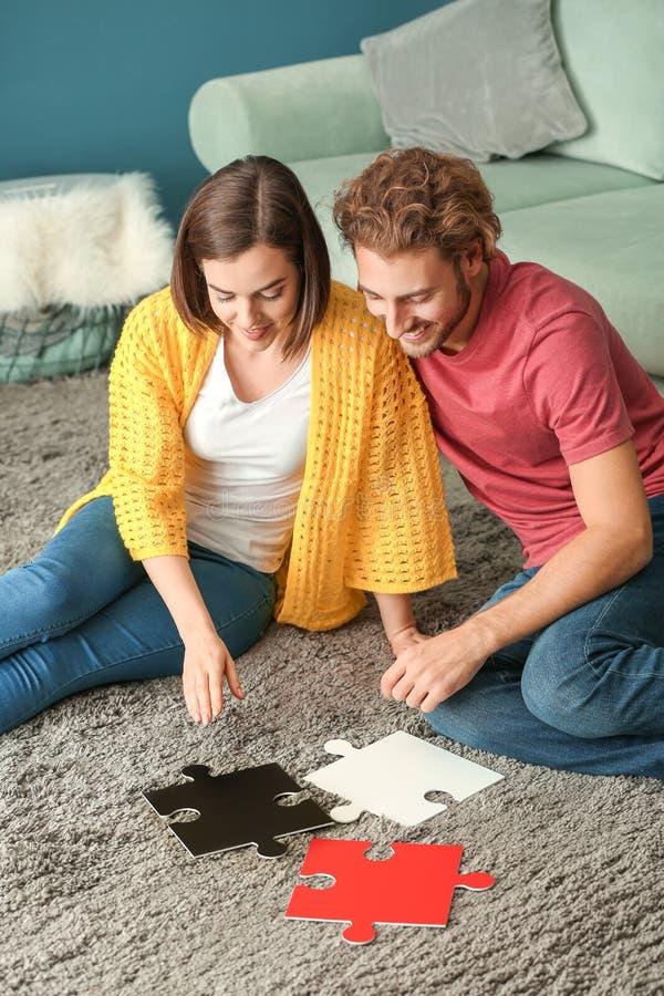 Jeunes ajouter aux morceaux de puzzle denteux à la maison photos libres de droits