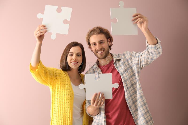 Jeunes ajouter aux morceaux de puzzle denteux sur le fond de couleur images stock