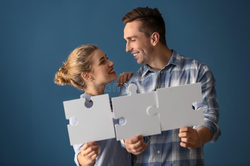 Jeunes ajouter aux morceaux de puzzle sur le fond de couleur photographie stock libre de droits