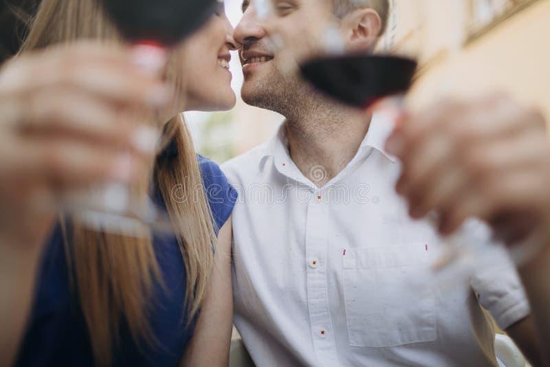 Jeunes ajouter aux verres de vin rouge dans un restaurant images stock