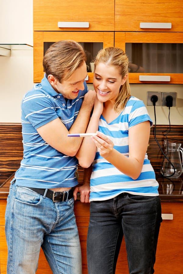 Jeunes ajouter heureux à l'essai de grossesse se tenant dans la cuisine image libre de droits