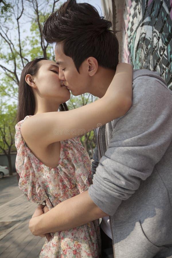 Jeunes ajouter heureux aux bras autour de l'un l'autre embrassant par un mur avec le graffiti photographie stock libre de droits
