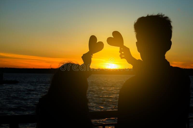 Jeunes ajouter heureux aux coeurs décoratifs sur la berge au coucher du soleil images libres de droits