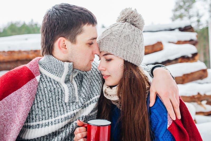 Jeunes ajouter romantiques à la boisson chaude dans des couples de forêt d'hiver dans l'amour photographie stock libre de droits