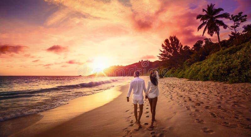 Jeunes amants heureux sur le coucher du soleil de plage photographie stock