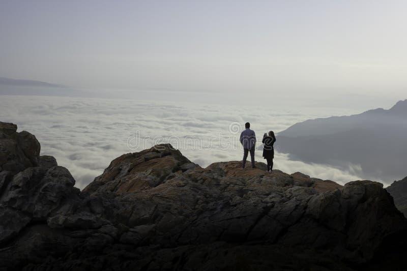 Jeunes amants sur un rocher admirant les montagnes photographie stock