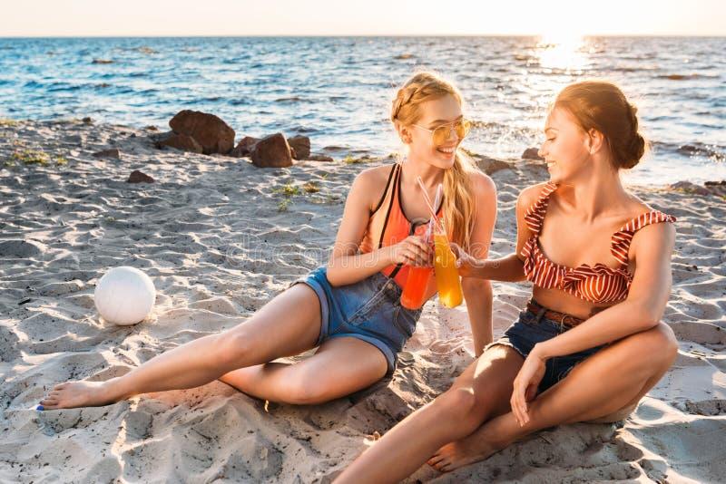 jeunes amies heureuses faisant tinter les bouteilles en verre avec des boissons d'été et se souriant sur la plage sablonneuse photos libres de droits