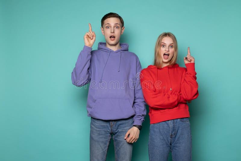 Jeunes amis émotifs stupéfiants de couples dans des vêtements sport posant avec la bouche ouverte se dirigeant avec des doigts photographie stock libre de droits