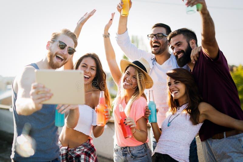 Jeunes amis ayant l'amusement à une partie de dessus de toit, jouant la guitare, le chant, la danse et le boire image libre de droits
