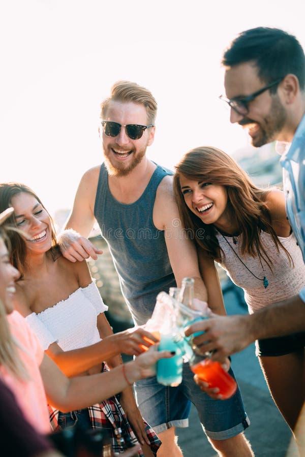 Jeunes amis ayant l'amusement à une partie de dessus de toit, jouant la guitare, le chant, la danse et le boire photo libre de droits