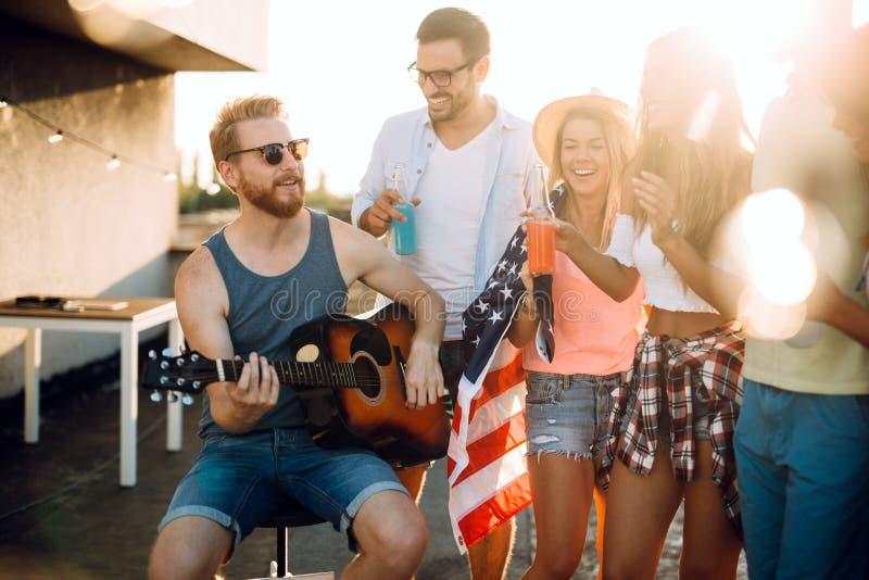 Jeunes amis ayant l'amusement à une partie de dessus de toit, jouant la guitare, le chant, la danse et le boire photographie stock