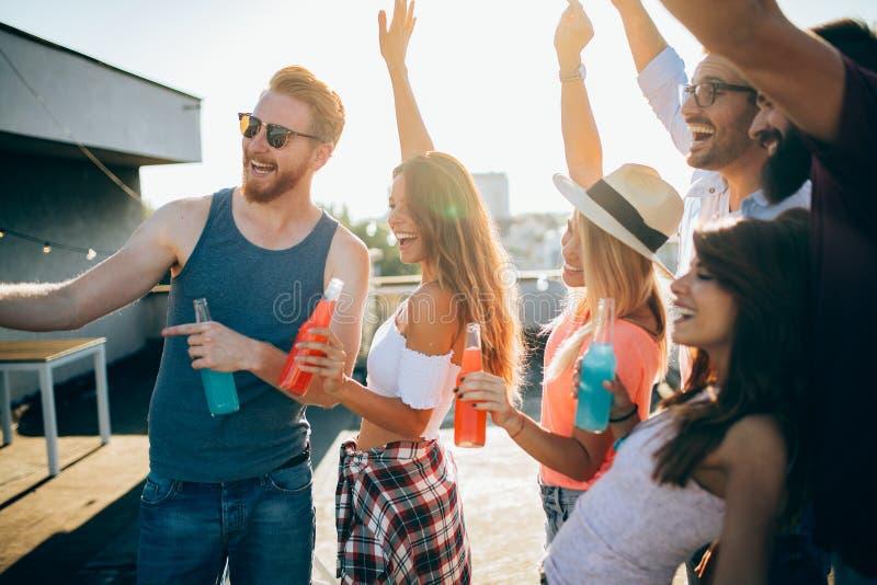 Jeunes amis ayant l'amusement à une partie de dessus de toit, jouant la guitare, le chant, la danse et le boire photo stock