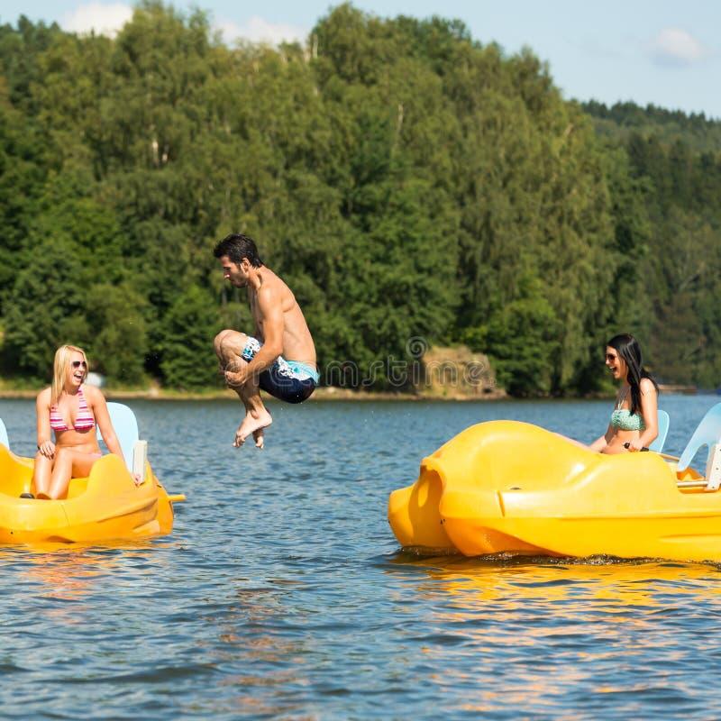 L'jeune homme sautant dans le bateau de palette de l'eau photos stock