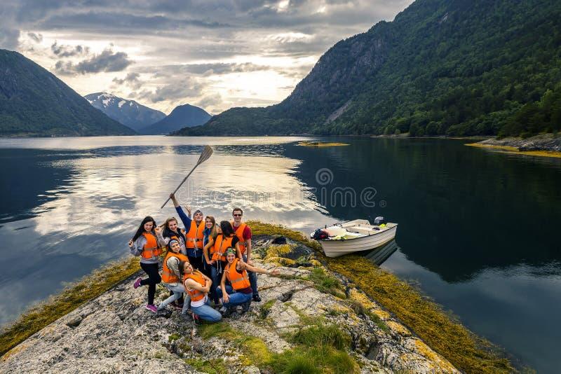 Jeunes amis ayant l'amusement sur le pique-nique sur l'île de la Norvège photos stock
