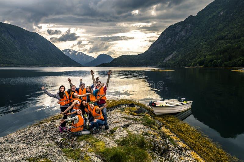 Jeunes amis ayant l'amusement sur le pique-nique sur l'île de la Norvège photographie stock libre de droits