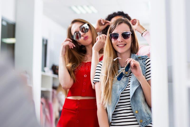 Jeunes amis féminins essayant sur des lunettes de soleil riant et ayant l'amusement dans la boutique accessoire images stock