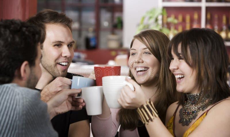 Jeunes amis grillant avec des cuvettes de café images libres de droits