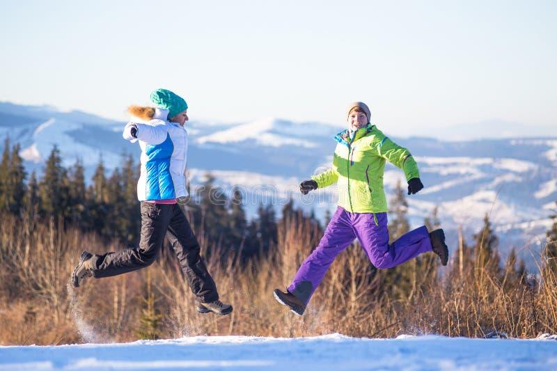 Jeunes amis heureux ayant l'amusement en montagnes d'hiver photo stock