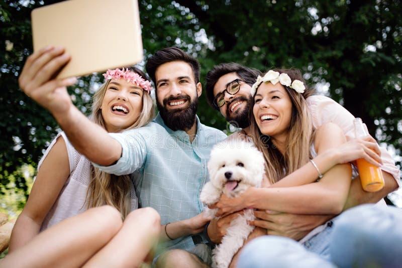 Jeunes amis heureux ayant l'extérieur d'amusement en nature, prenant le selfie photo libre de droits