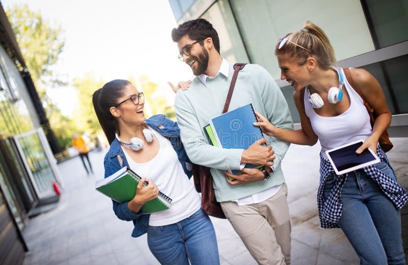 Jeunes amis heureux d'?tudiants ?tudiant avec des livres ? l'universit? photos stock