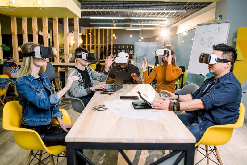 Jeunes amis heureux examinant des jeux vidéo portant les personnes gaies en verre de réalité virtuelle à l'intérieur - ayant l'am image stock