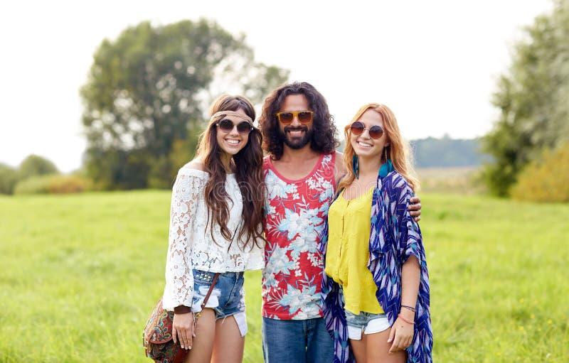 Jeunes amis hippies de sourire sur le champ vert photo stock