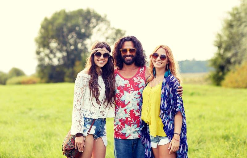 Jeunes amis hippies de sourire sur le champ vert images libres de droits