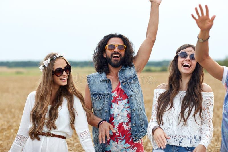 Jeunes amis hippies heureux dansant sur le gisement de céréale images stock