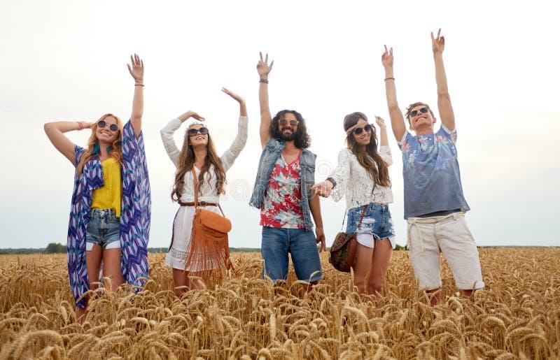 Jeunes amis hippies heureux dansant sur le gisement de céréale image libre de droits