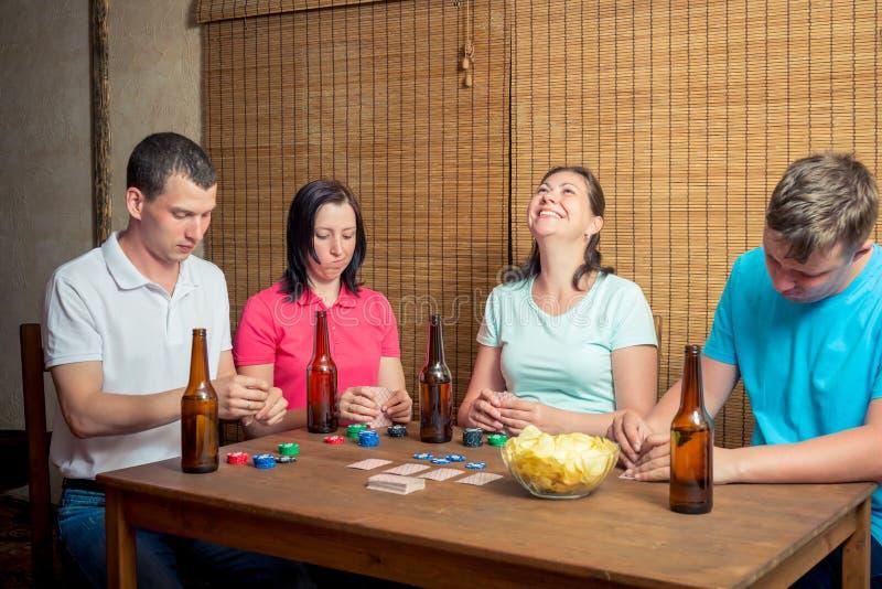 Jeunes amis jouant des cartes se reposant à une table à l'intérieur, buvant photo stock
