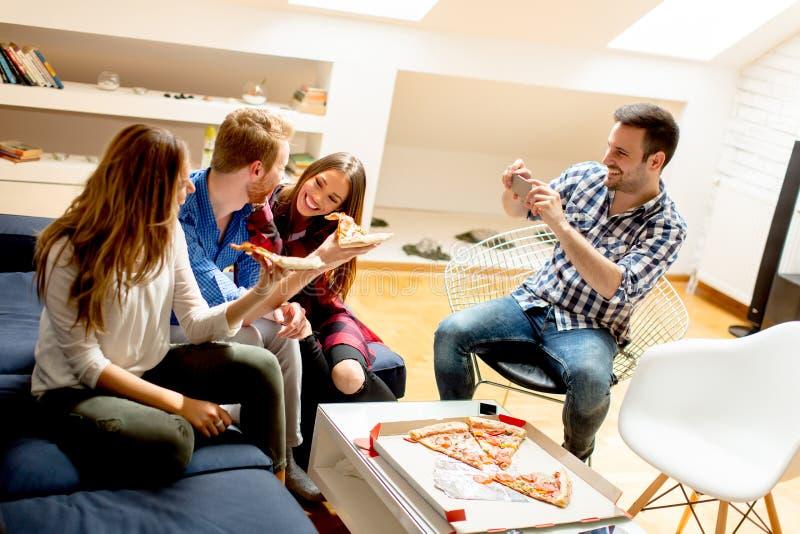 Jeunes amis mangeant de la pizza à la maison et ayant l'amusement photo libre de droits