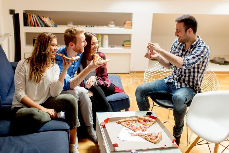 Jeunes amis mangeant de la pizza à la maison et ayant l'amusement images libres de droits