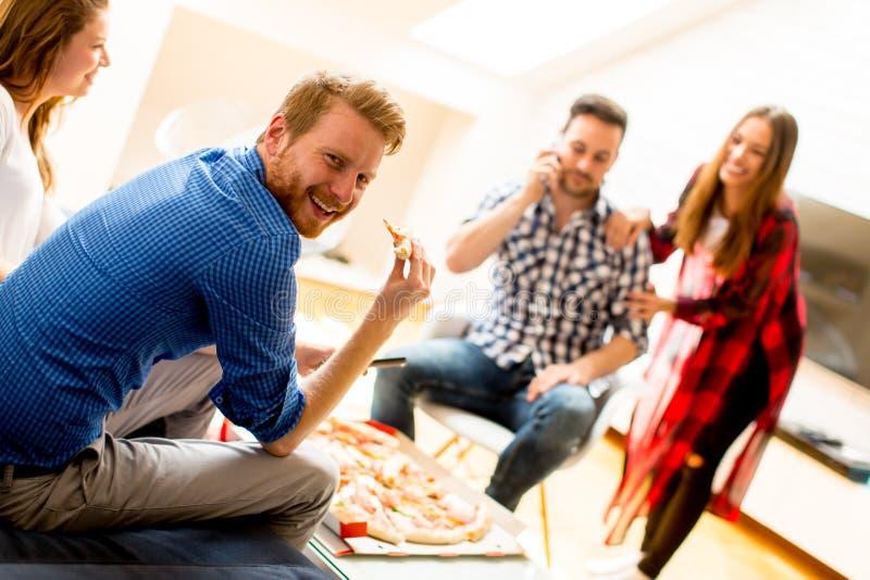 Jeunes amis mangeant de la pizza à la maison et ayant l'amusement image libre de droits