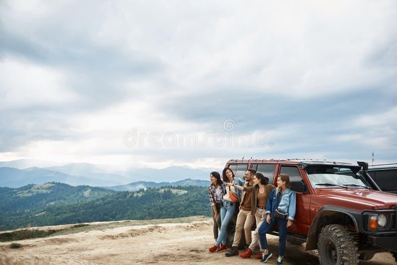 Jeunes amis positifs appréciant le week-end dans les montagnes photo stock