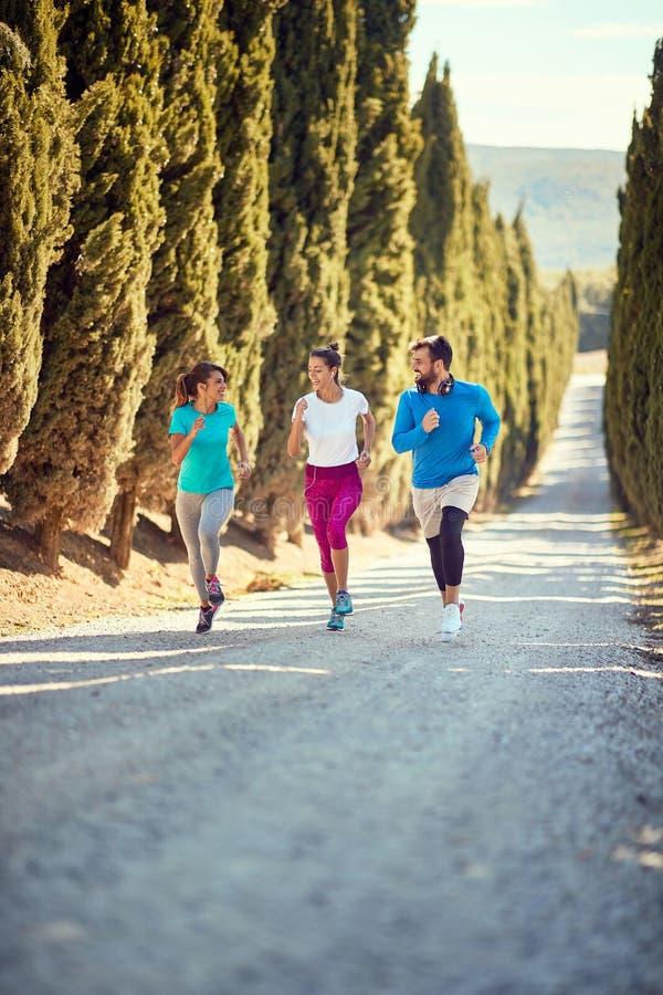 Jeunes amis qui aiment courir ensemble en plein air images libres de droits