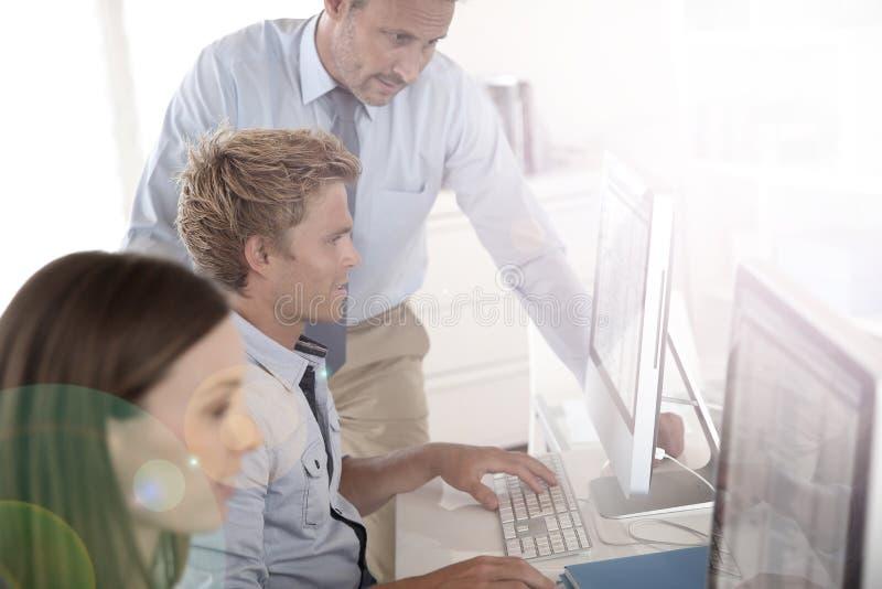 Jeunes apprentis dans la formation avec l'instructeur au bureau image stock